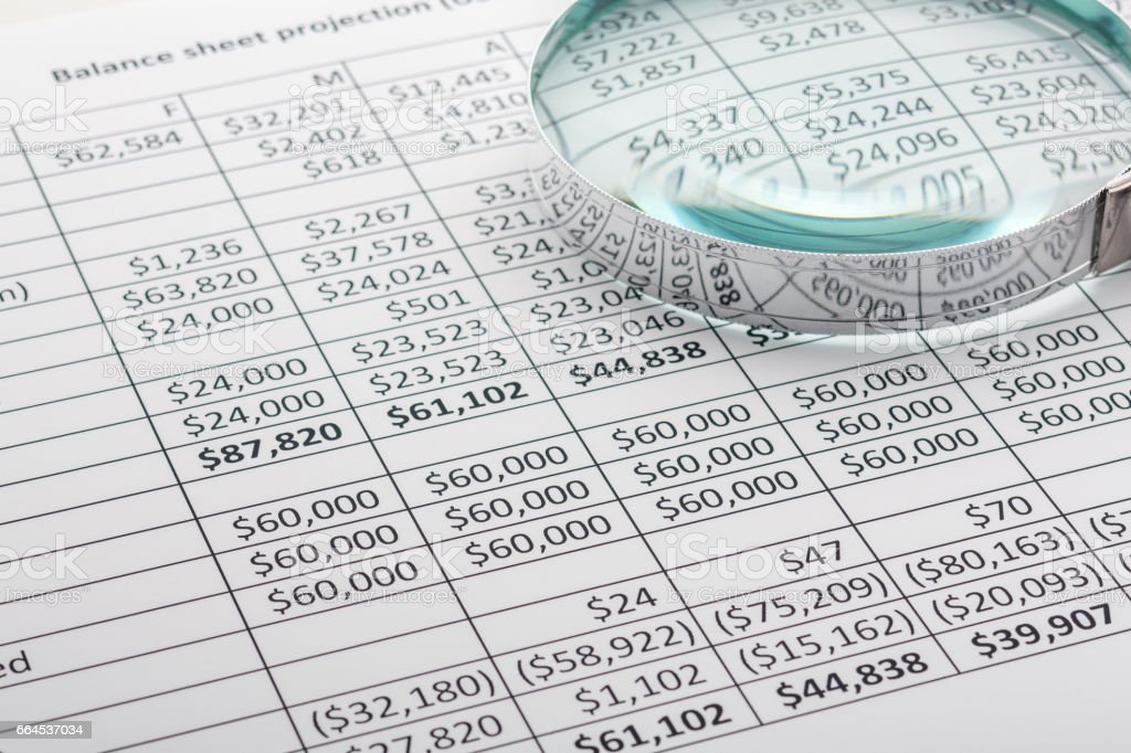 Close up of finance business sheet with magnifying glass stock photo