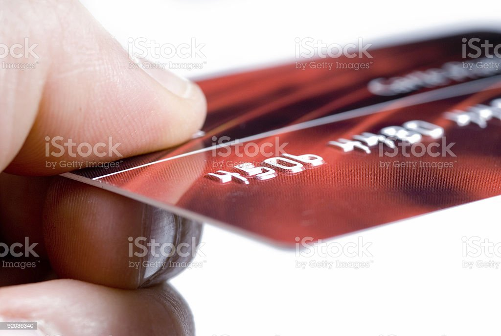 Close up of fingers holding a red credit card royalty-free stock photo