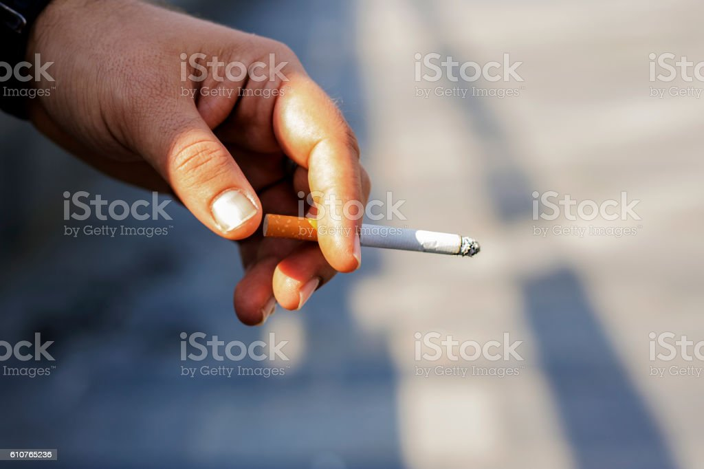 Close up of fingers holding cigarette stock photo