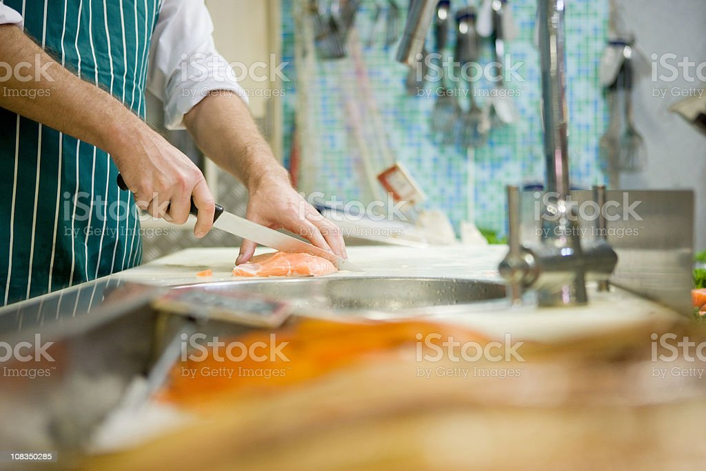 Close up of fishmonger cutting fish stock photo