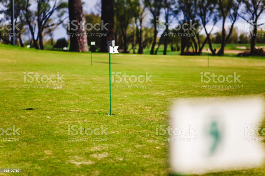 close up of flag mark in hole on golf field stock photo