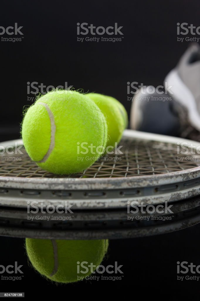 Close up of fluorescent yellow tennis balls on racket by sports shoes...