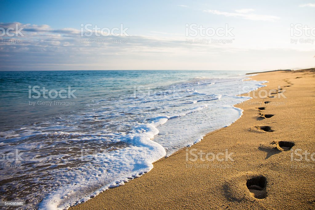 close up of footprints in the sand at sunset stock photo