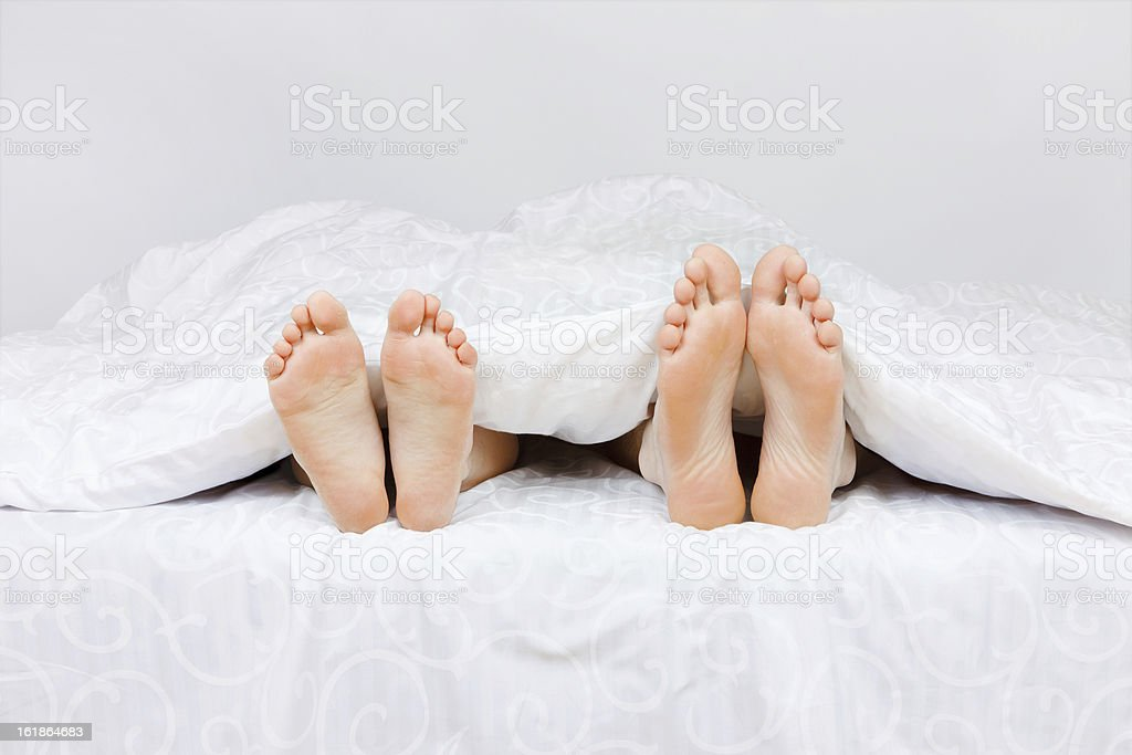 Close up of four feet in a bed royalty-free stock photo