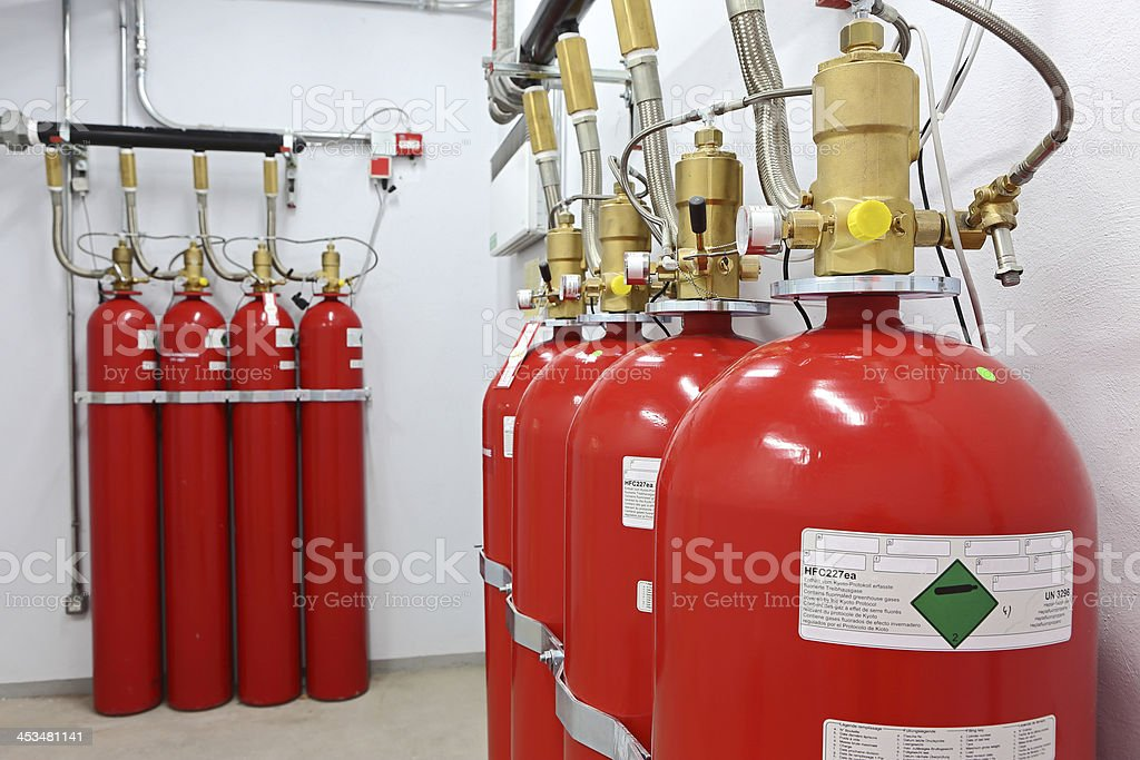 Close up of four fire extinguishers with four more behind stock photo