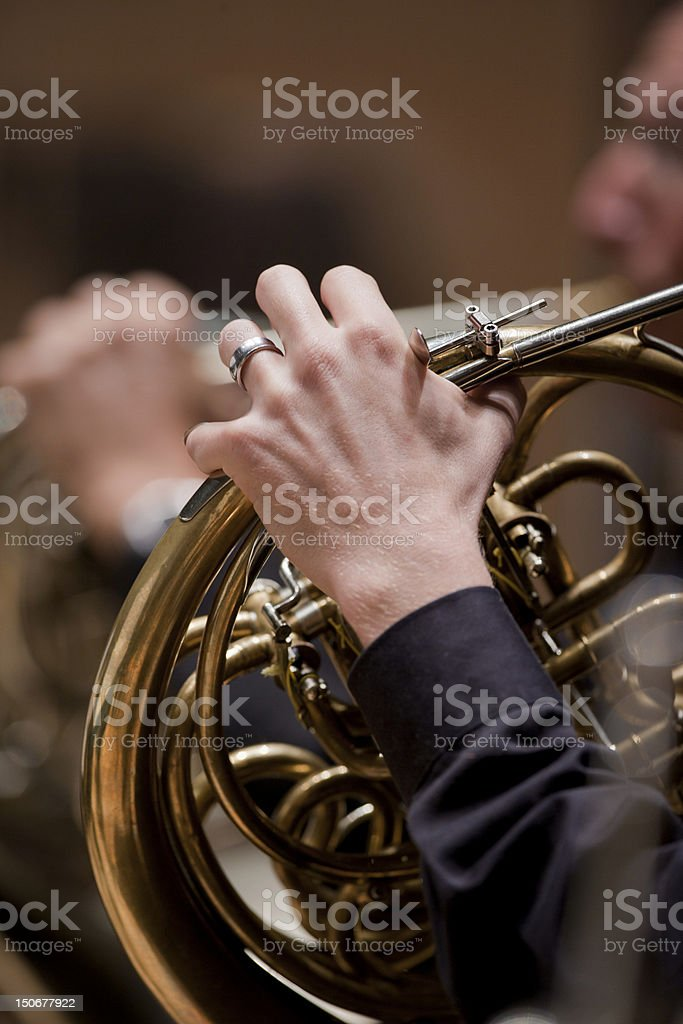 Close up of French horn player in orchestra stock photo