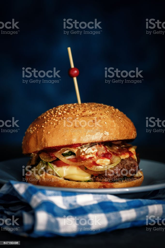 Close Up of Fresh Burger on Dark Rustic Wooden Surface with Blue Background stock photo