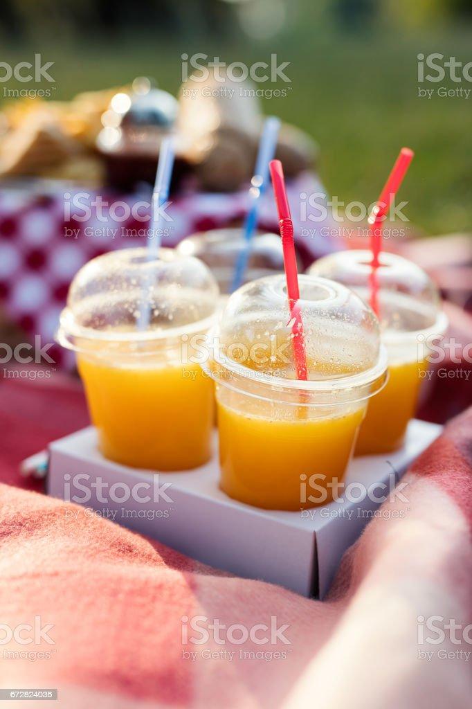 Close up of fresh orange juice in plastic cups. stock photo