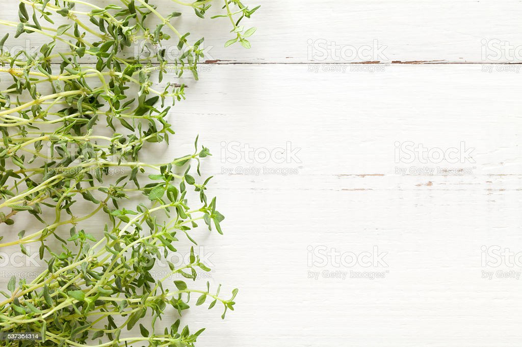 Close up of fresh thyme on white wooden table stock photo
