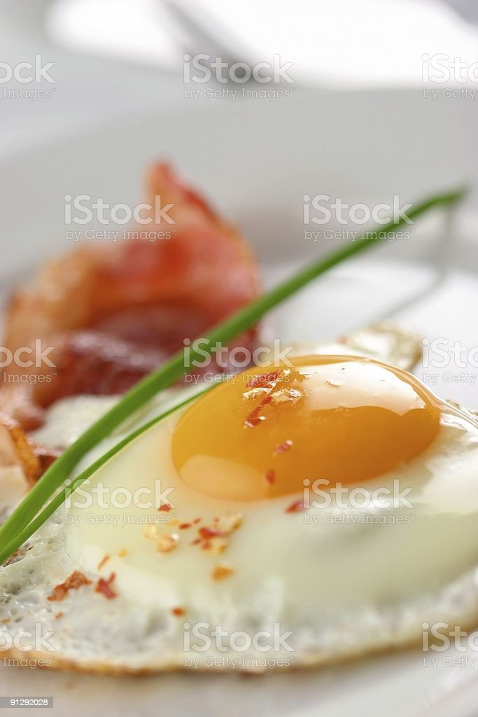 Close up of fried egg with bacon in background stock photo
