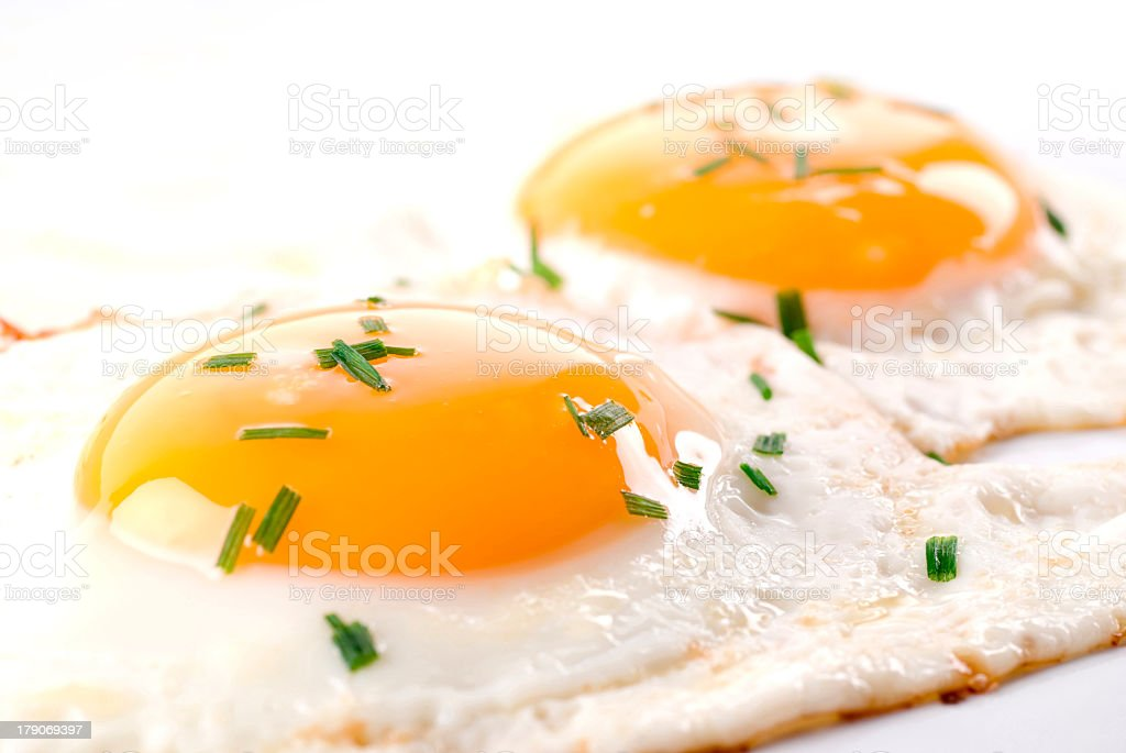 A close up of fried eggs with seasonings stock photo