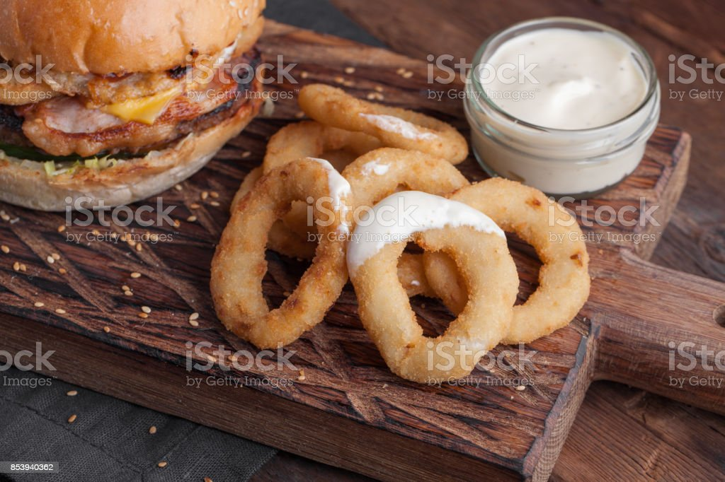 Close up of fried onion rings on the Board, with a white garlic sauce on wooden background stock photo