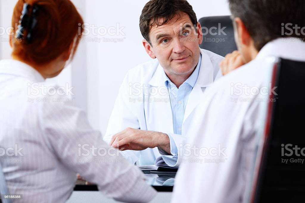 close up of friendly mature Doctor talking with concerned couple stock photo
