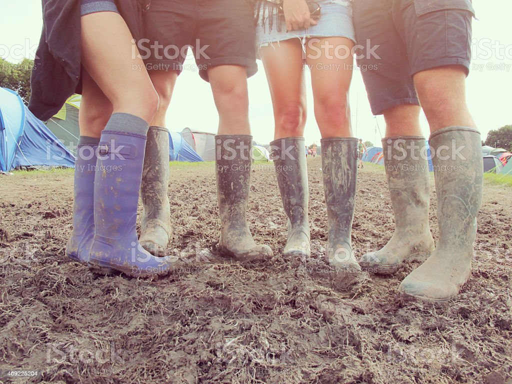 Close Up Of Friends In Wellington Boots Walking To Festival stock photo