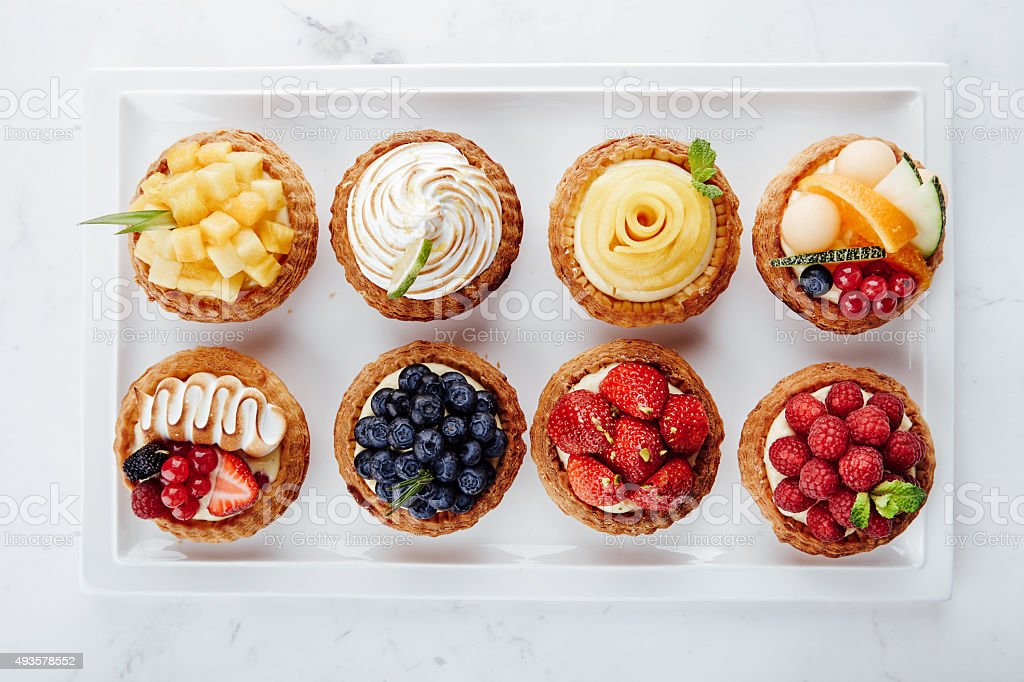 Close up of fruit tarts and various desserts stock photo