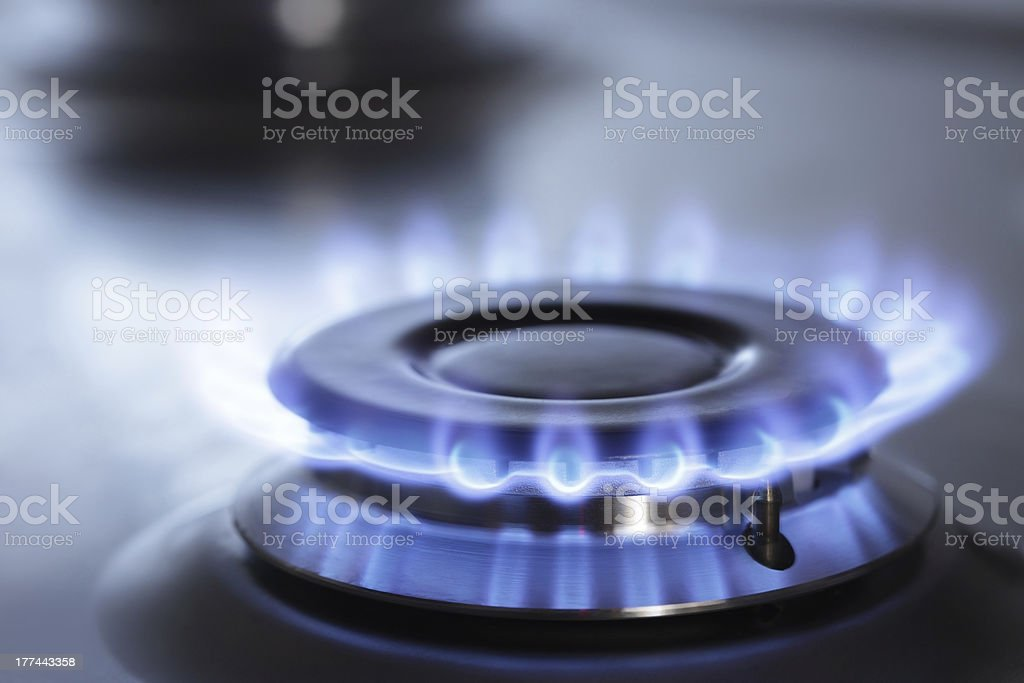 Close up of gas stove with blue flames stock photo