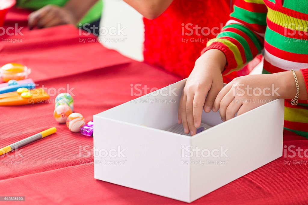 Close up of girls hands while working on Christmas project stock photo