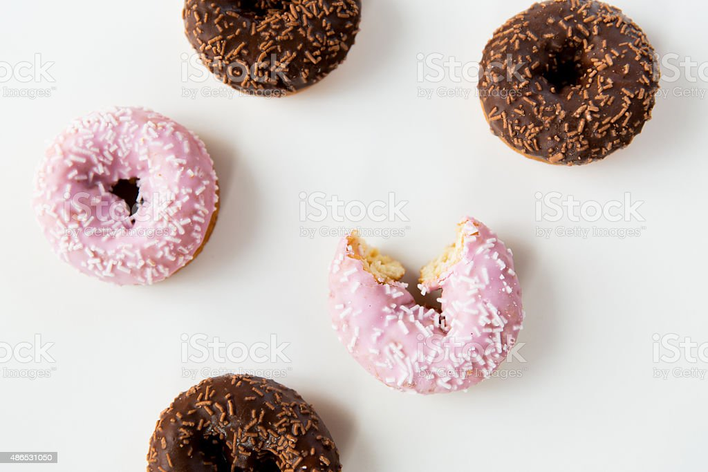 close up of glazed donuts pile over white stock photo