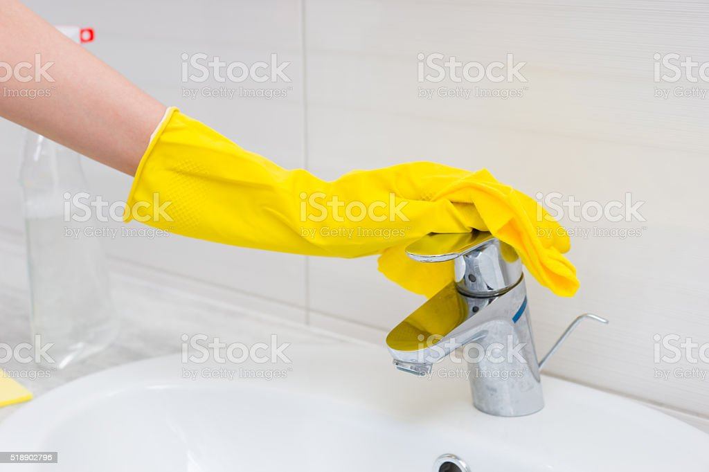 Close up of gloved hand cleaning sink stock photo