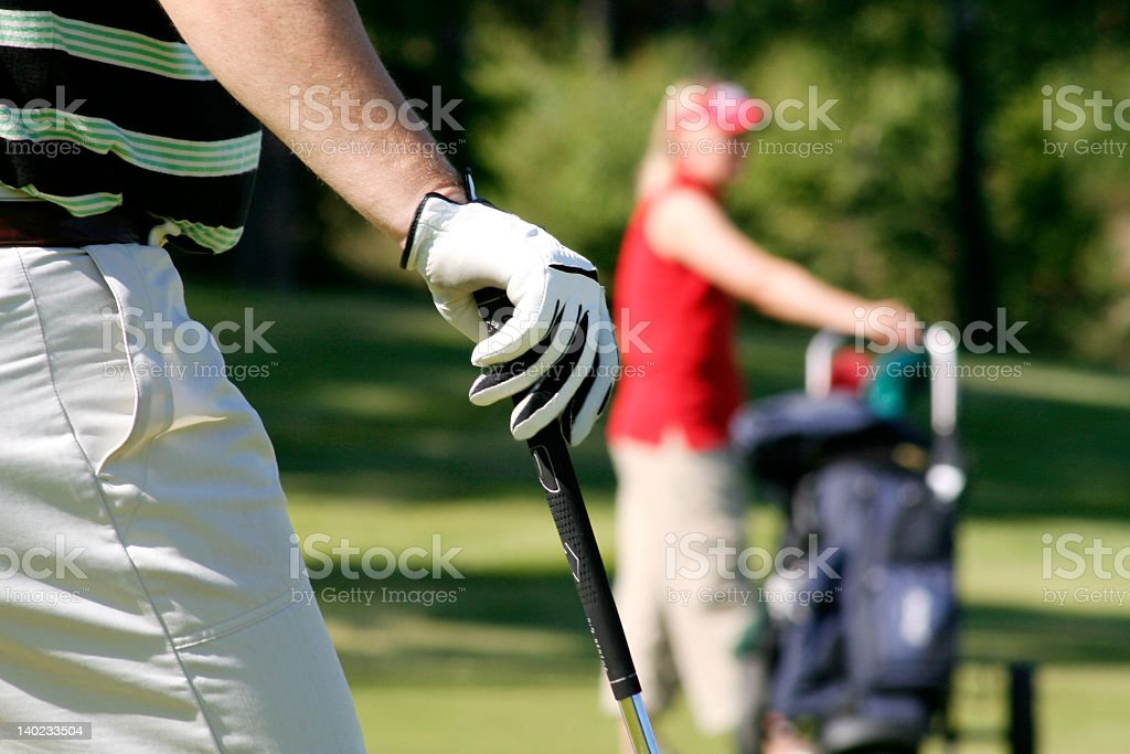 Close up of gloved hand resting on golf club stock photo