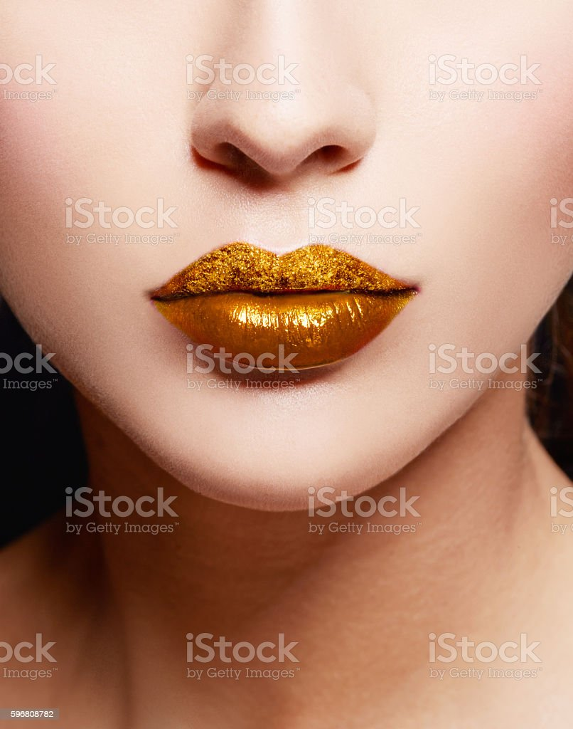 Close up of gold artistic lips. Makeup cosmetic image. stock photo