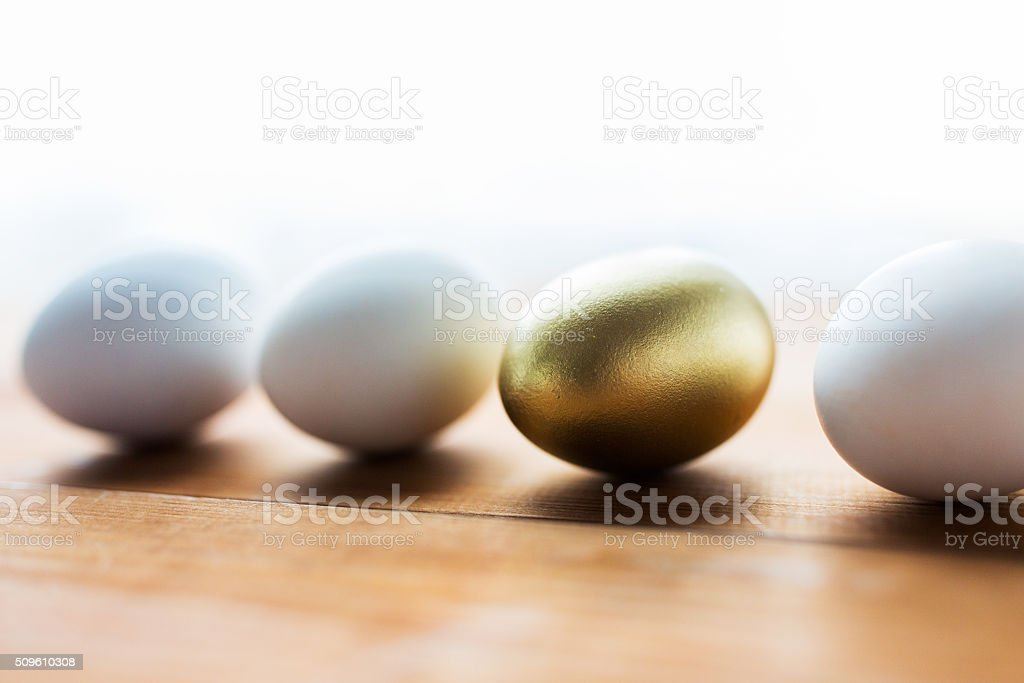 close up of golden and white easter eggs on wood stock photo