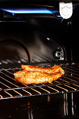 Close up of golden chicken breast on grill