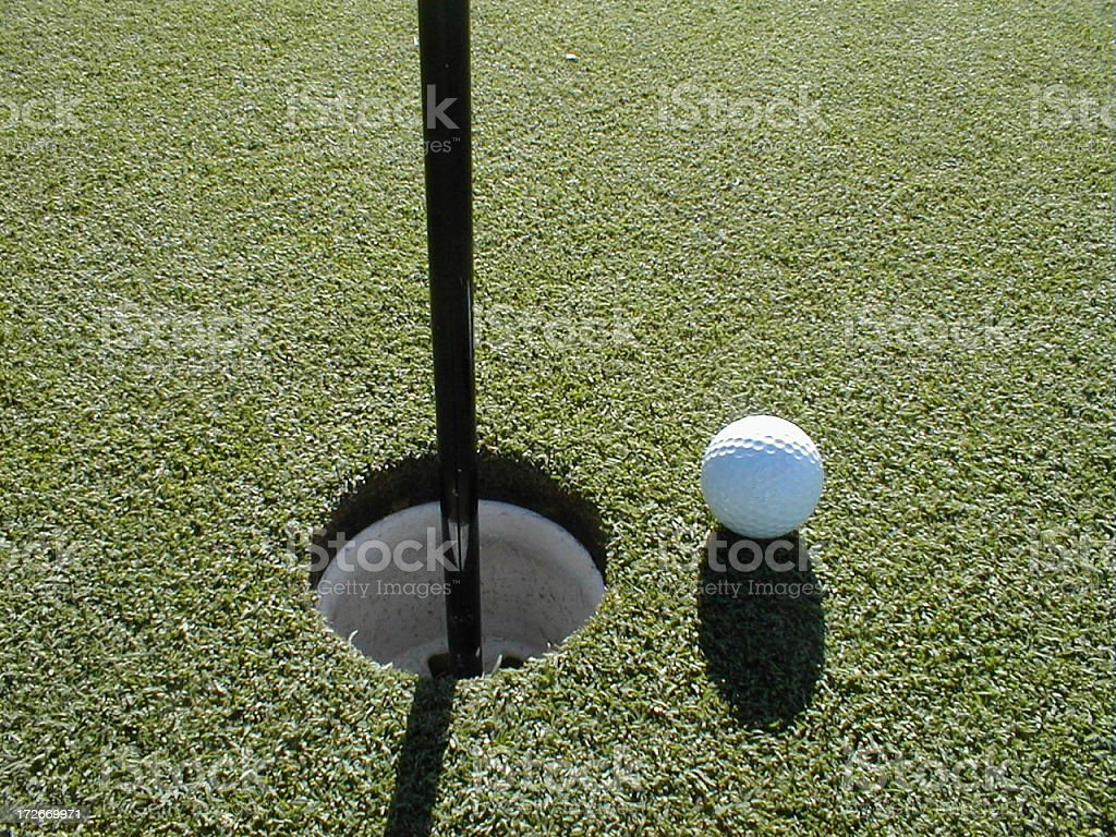 Close up of golf ball and cup stock photo