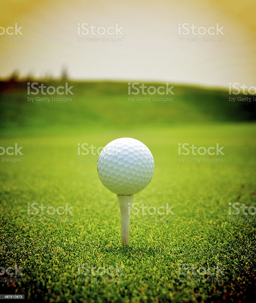 Close up of golf ball with tee on grass stock photo