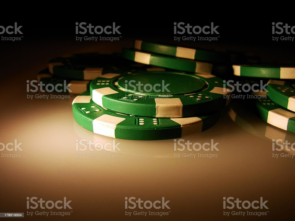 Close up of green and white poker chips in shadow stock photo