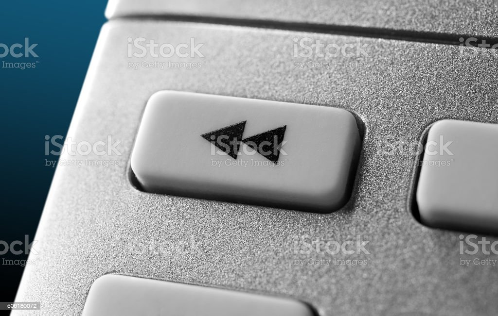 Close Up Of Grey Rewind Button On Chrome Remote Control stock photo