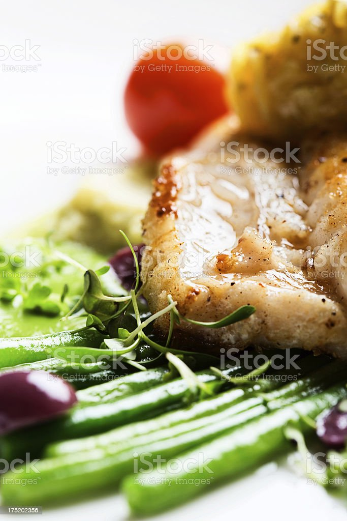 Close up of grilled fish with green beans and olives stock photo