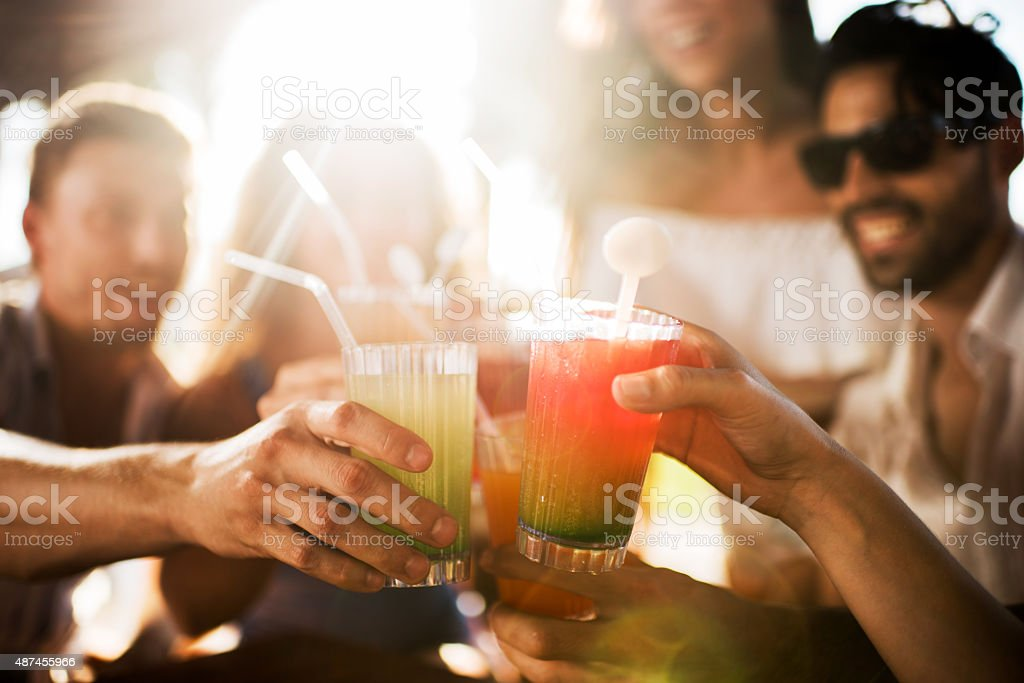 Close up of group of friends toasting with cocktails. stock photo