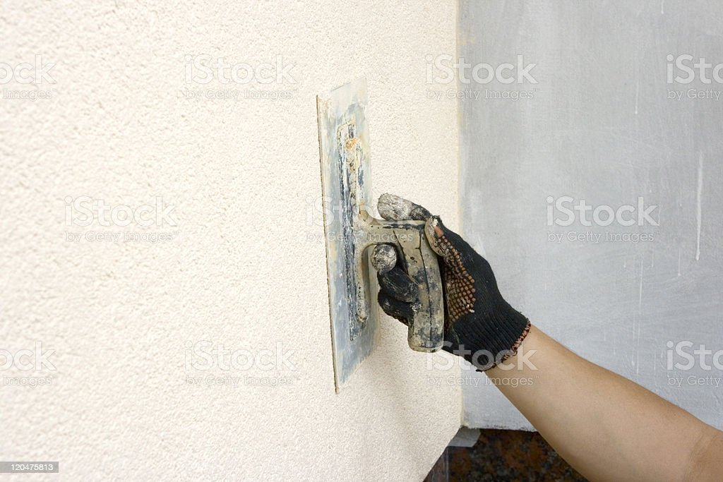 Close up of hand applying plaster to wall royalty-free stock photo