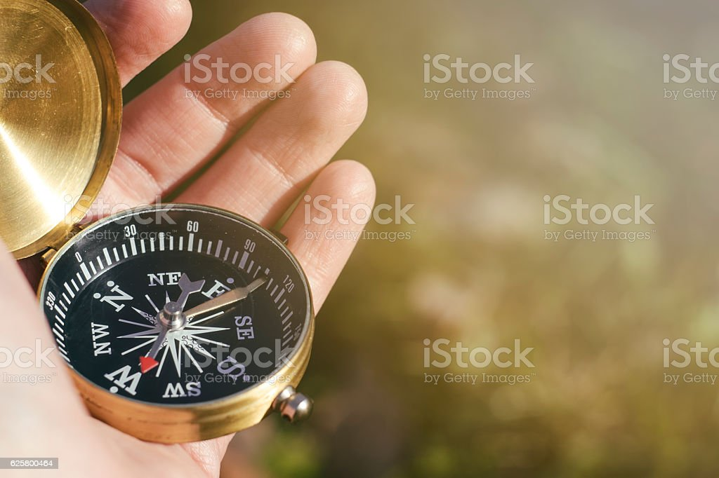 Close up of hand holding compass stock photo