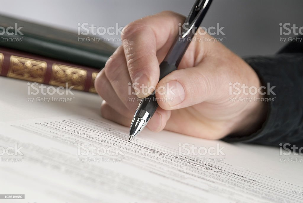 Close up of hand holding pen signing a document stock photo