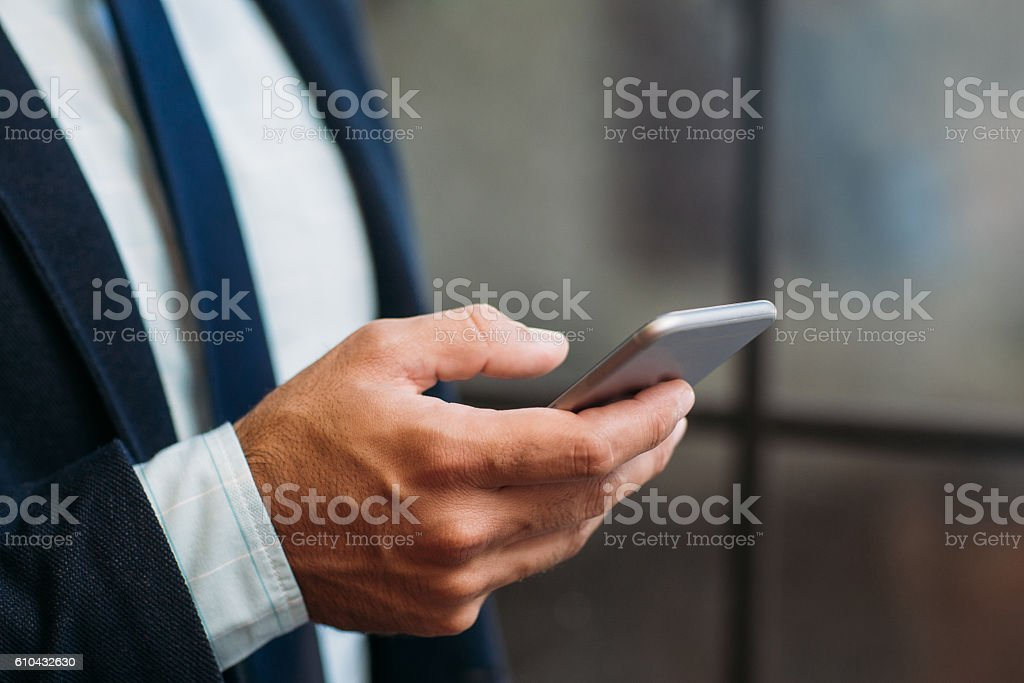 Close up of hand holding smartphone stock photo