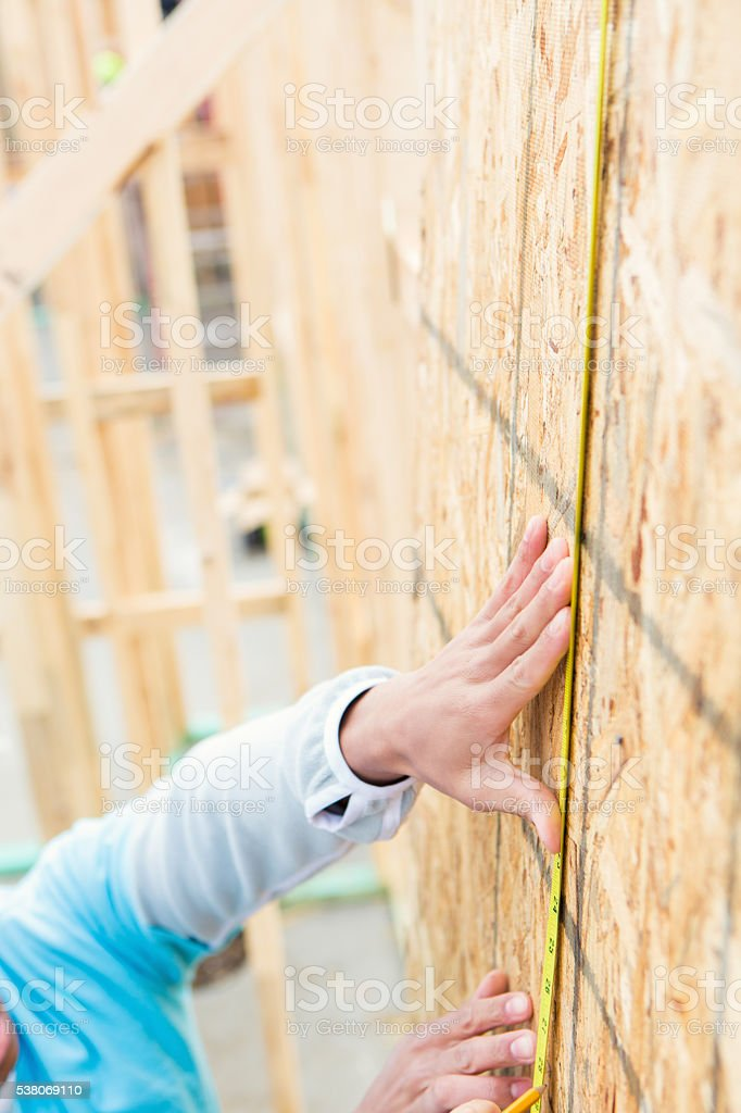 Close up of hand measuring plywood stock photo