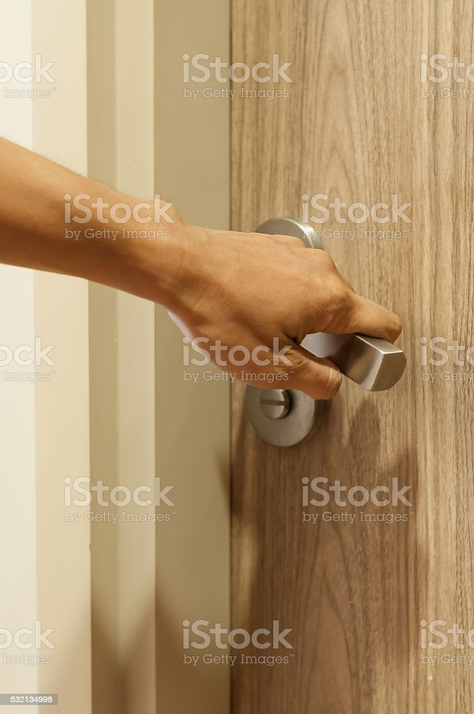 Close up of hand of man is  turning door handle. stock photo