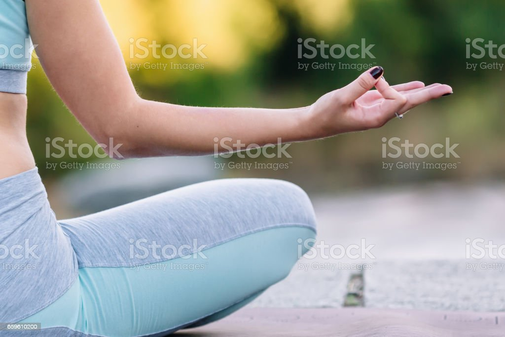 Close up of hand of young woman sitting in lotus pose stock photo