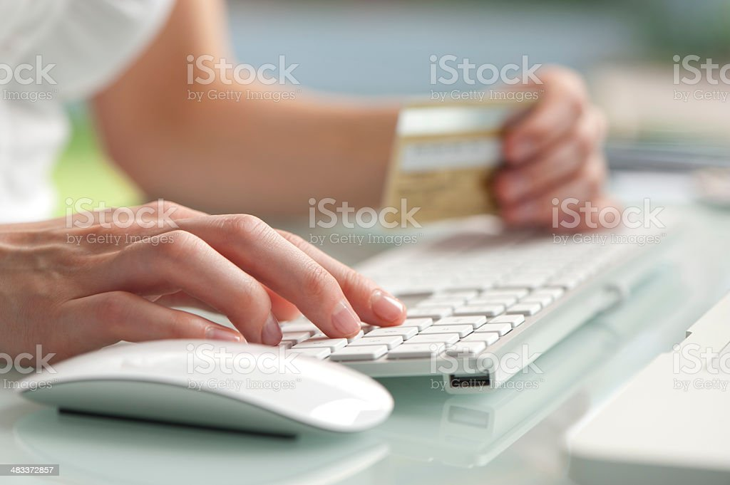 Close up of hand on keyboard entering credit card stock photo