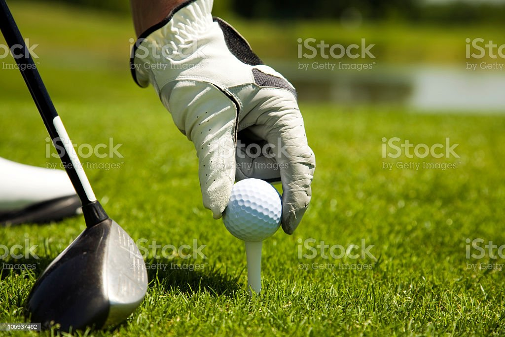 Close up of hand placing golf ball on tee with golf club stock photo