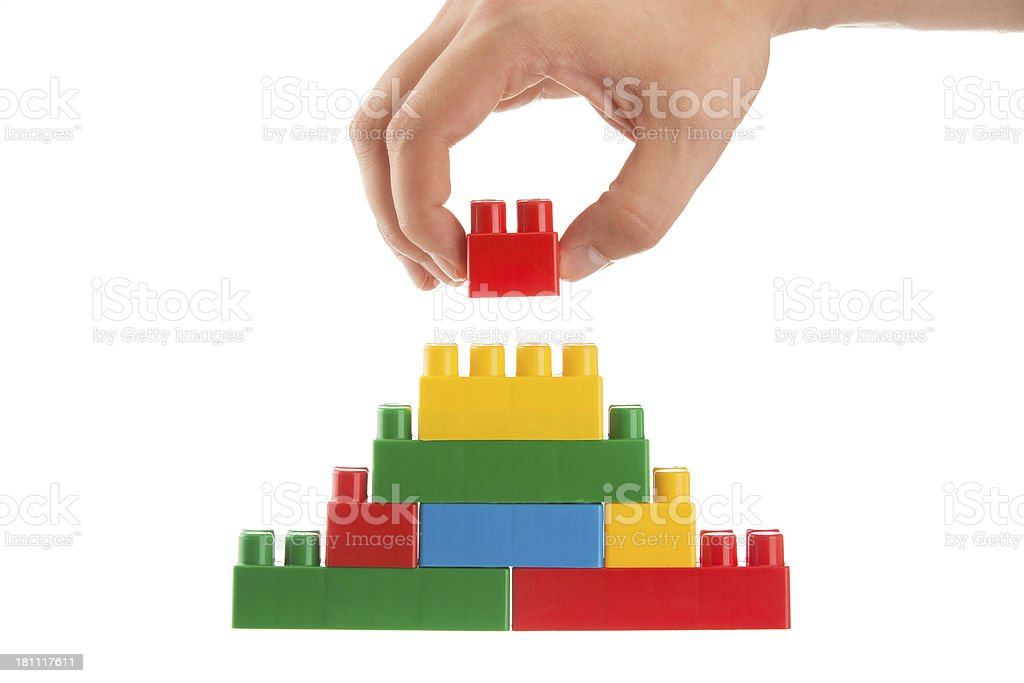 Close up of hand placing the top block onto a toy pyramid stock photo
