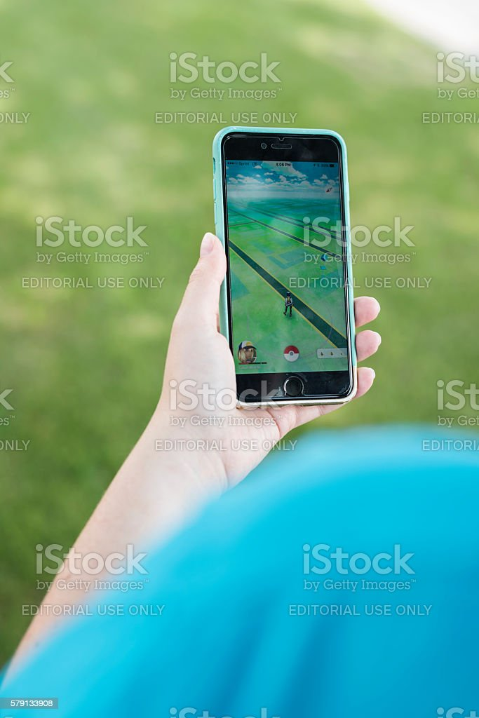 Close up of hand playing Pokemon GO on smartphone stock photo