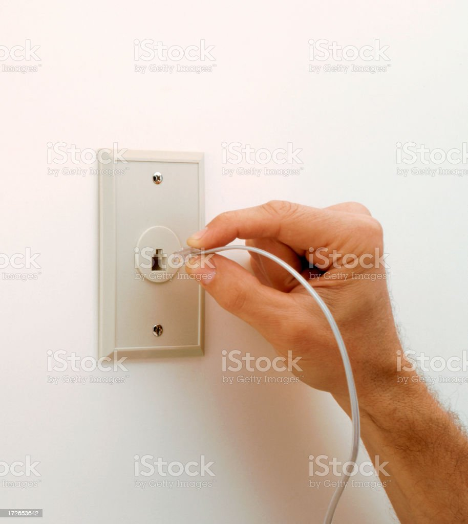 Close up of hand plugging line in a telephone jack royalty-free stock photo