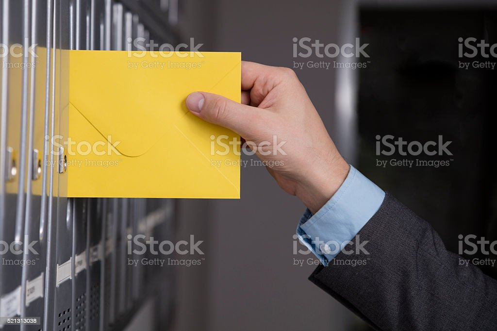 Close up of hand putting the yellow letter into the mailbox stock photo