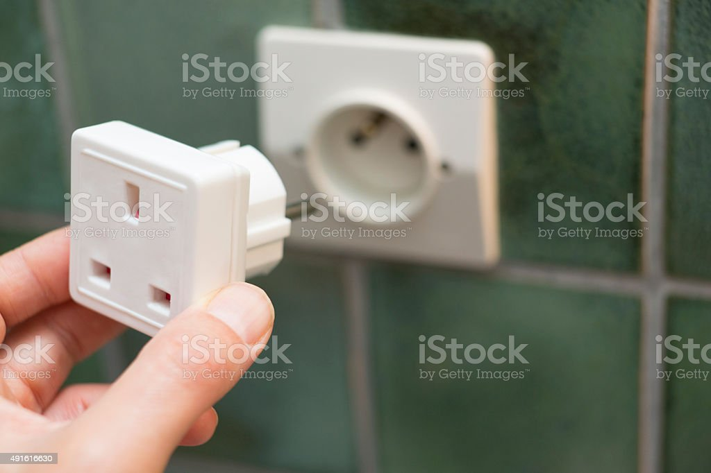 Close Up Of Hand Putting Travel Adapter Into Socket stock photo