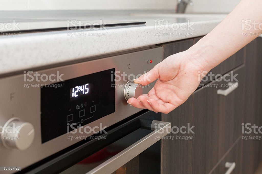 Close Up Of Hand Setting Temperature Control On Oven stock photo