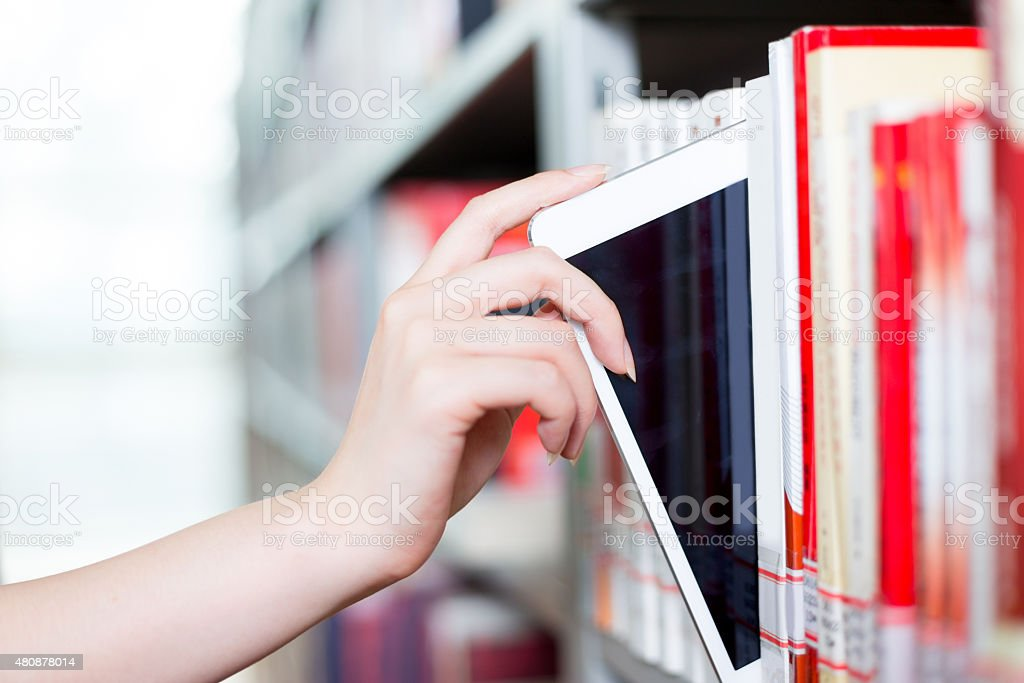 close up of hand touching tablet in library stock photo
