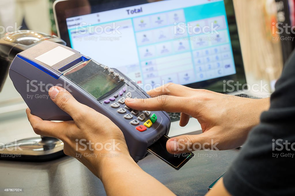 Close Up Of Hand With Credit Card Swipe Through Terminal stock photo
